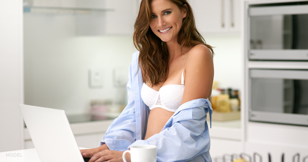 A woman researches breast augmentation questions on her laptop.